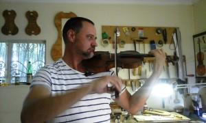 Albertus toets een van die viole wat hy gebou het.